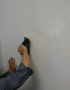 Using a trowel, apply vinyl tread adhesive to the wall, covering the whole area where the first panel is going. (You marked the wall right?)